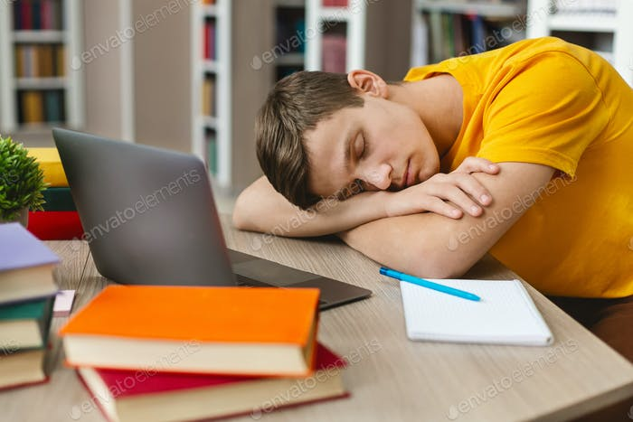 Exhausted student sleeping on workplace in front of laptop