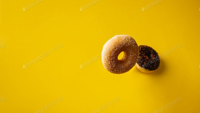 Various decorated doughnuts in motion falling on yelloy background