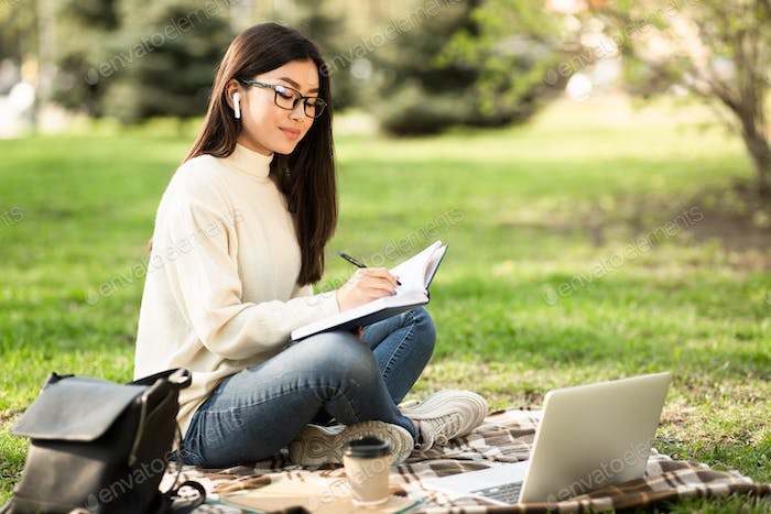 Girl writing in diary, sitting in parkland
