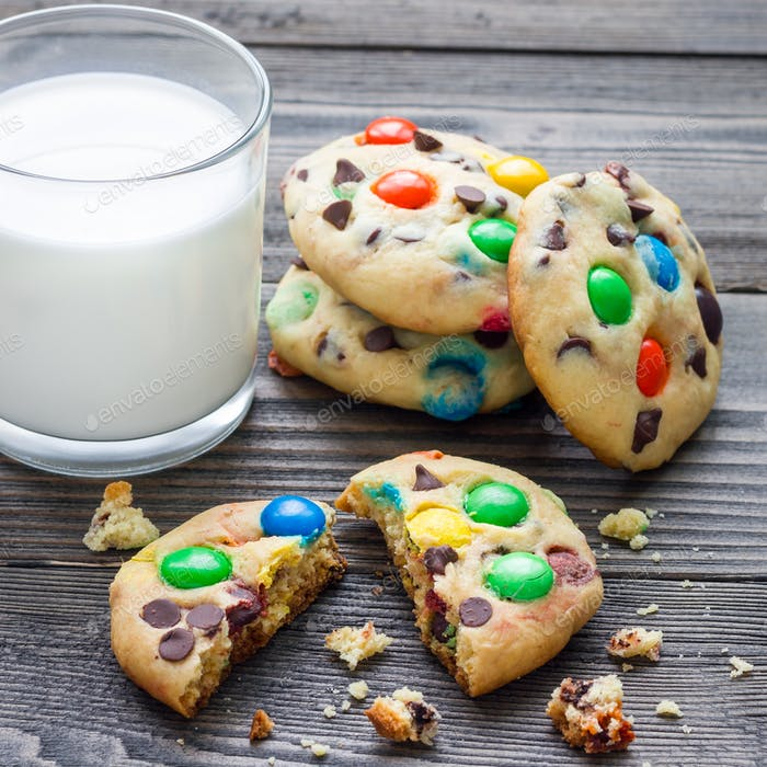 Shortbread cookies with multi colored candy and chocolate chips, served with glass of milk, square