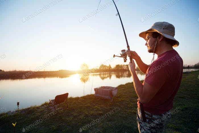 Young man fishing at pond and enjoying hobby