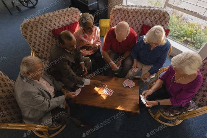 High angle view of group of senior friends playing cards at nursing home