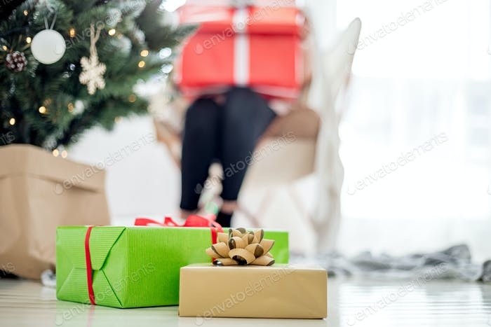 Christmas gifts under Xmas tree in bright white room