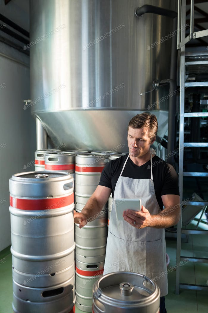 Worker holding digital tablet examining kegs