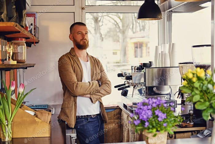 A man in a small cafe with a lot of flowers and coffee machine.