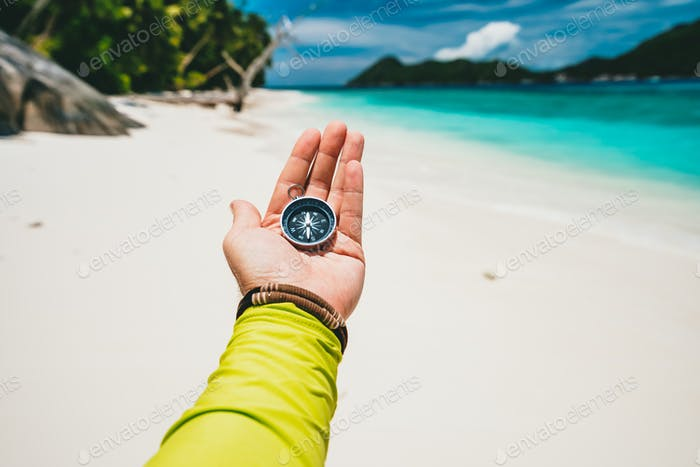 Male hand holding compass on tropical sandy beach and ocean. POV travel holiday adventure concept