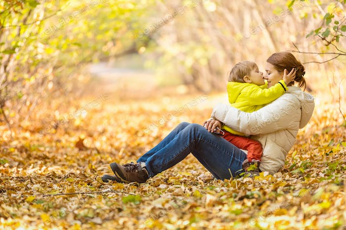 Happy woman and her little son having fun in an autumn park.