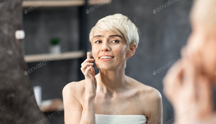 Beautiful Lady Applying Cream On Face Standing In Bathroom, Panorama