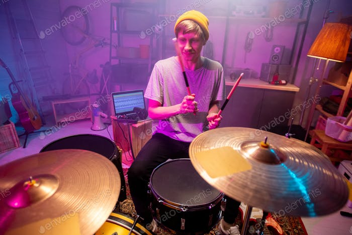 Young musician going to beat cymbals with drumsticks while making new music