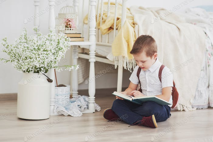 Cute little boy is going to school for the first time. Child with bag and book