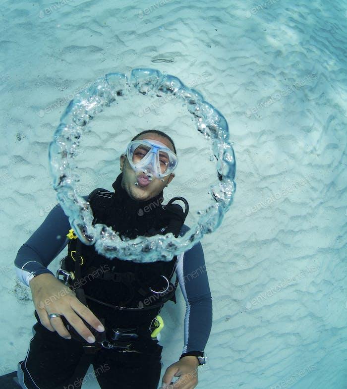 Scuba diver blowing bubble rings underwater