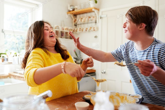 Young Downs Syndrome Couple Having Fun Baking Cupcakes In Kitchen At Home