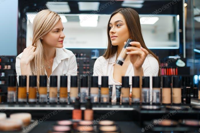 Cosmetician and woman choosing nail varnish