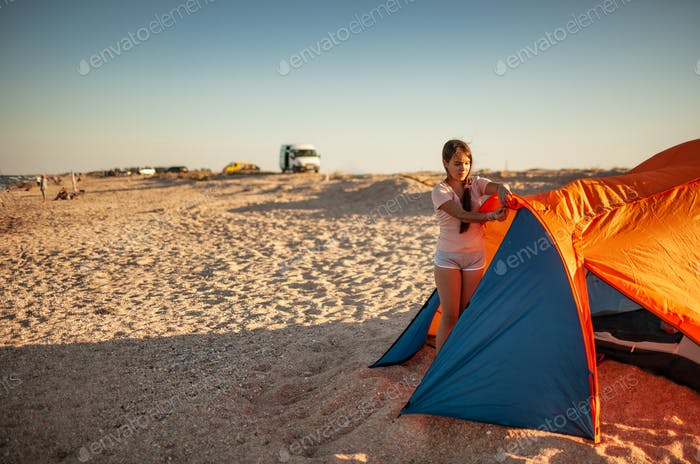 Beautiful young girl with dark hair sets up a tent on the beach