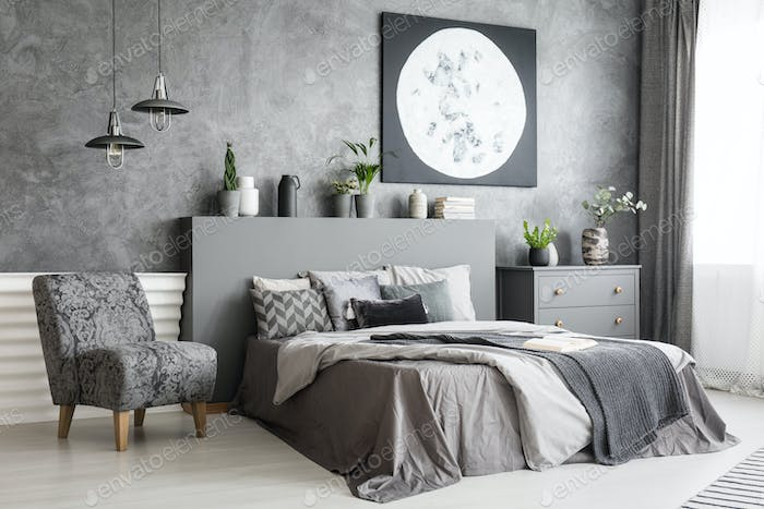 Armchair next to bed in grey bedroom interior with moon poster o