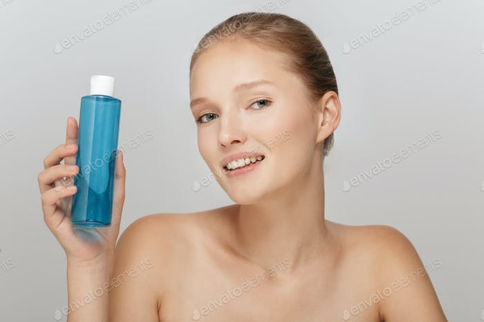 Portrait of beautiful smiling woman without makeup holding blue