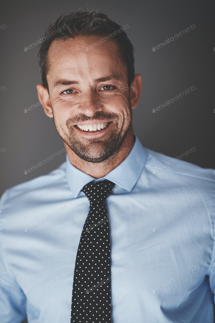 Smiling young executive standing against a gray background