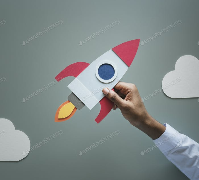 Hand holding rocketship startup business