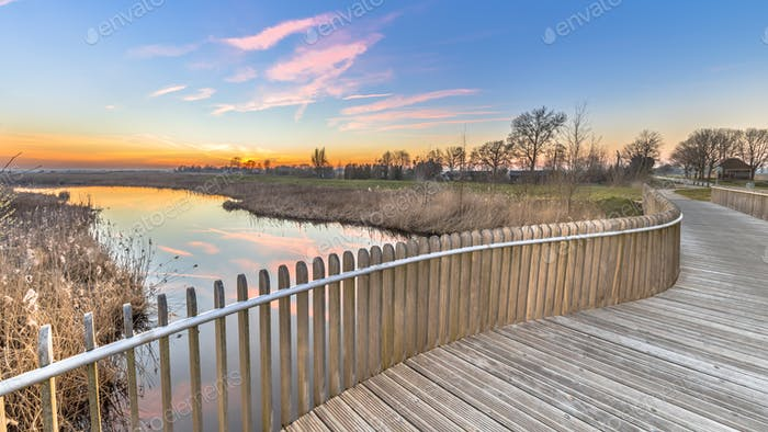 Plankied balustrade sunset over swamp