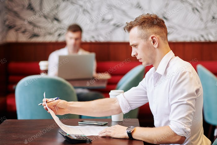 Young entrepreneur sitting at cafe table and making calculations