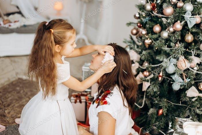 Charming little daughter in nice dress put a flower in mothers hair near the New Year's tree