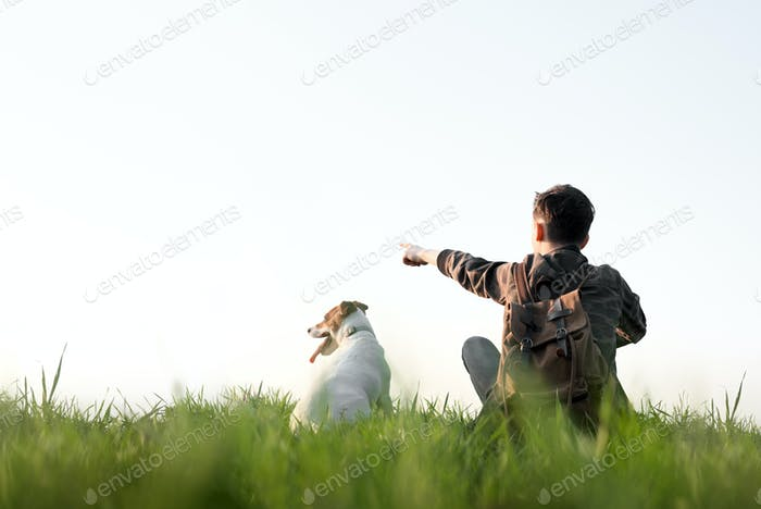 Teenager on green lawn with small white dog
