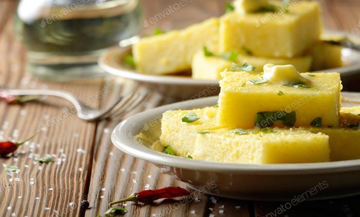 Polenta mit Butter und Grüns auf Tonschale auf rustikalem Holz-Tab