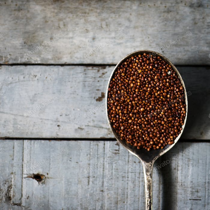 Quinoa in spoon with wooden textured
