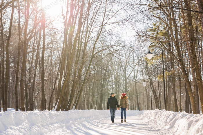Young couple in love walking in the snowy forest
