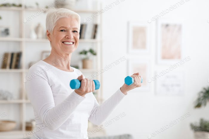 Cheerful senior woman exercising with dumbbells at home, enjoying active healthy lifestyle