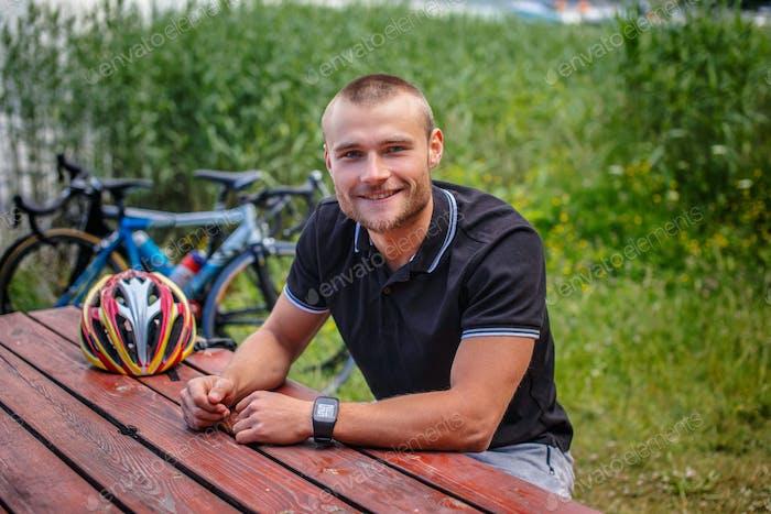 Smiling man sitting at table on lake shore
