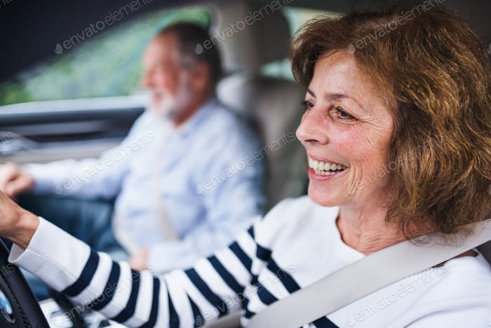 Happy senior couple sitting in car, driving and talking