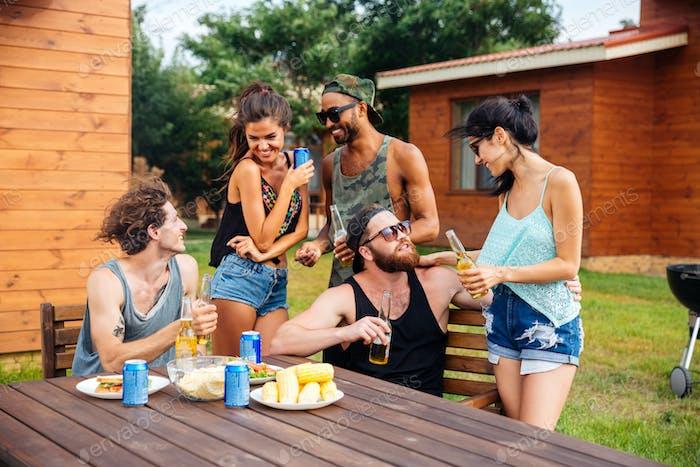 Group of teenage friends drinking beer and eating snacks