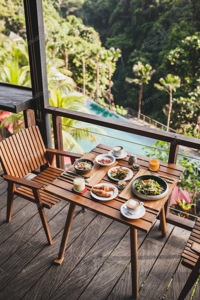Table with served breakfast on wooden terrace with pool and jungle view in Bali
