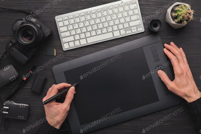 Designer hand with graphic tablet and keyboard