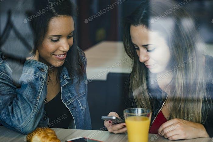 dos amigas de raza mixta tener un café y charlar