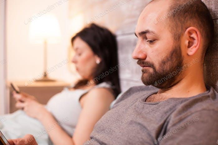 Man reading in bed with wife