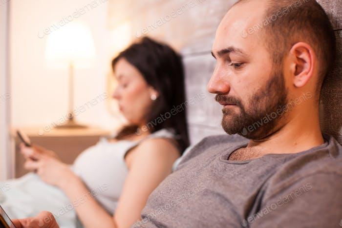 Мужчина читает в постели с женой