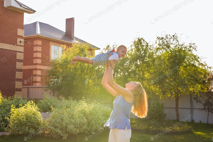 Playful woman in the garden playing with her baby son