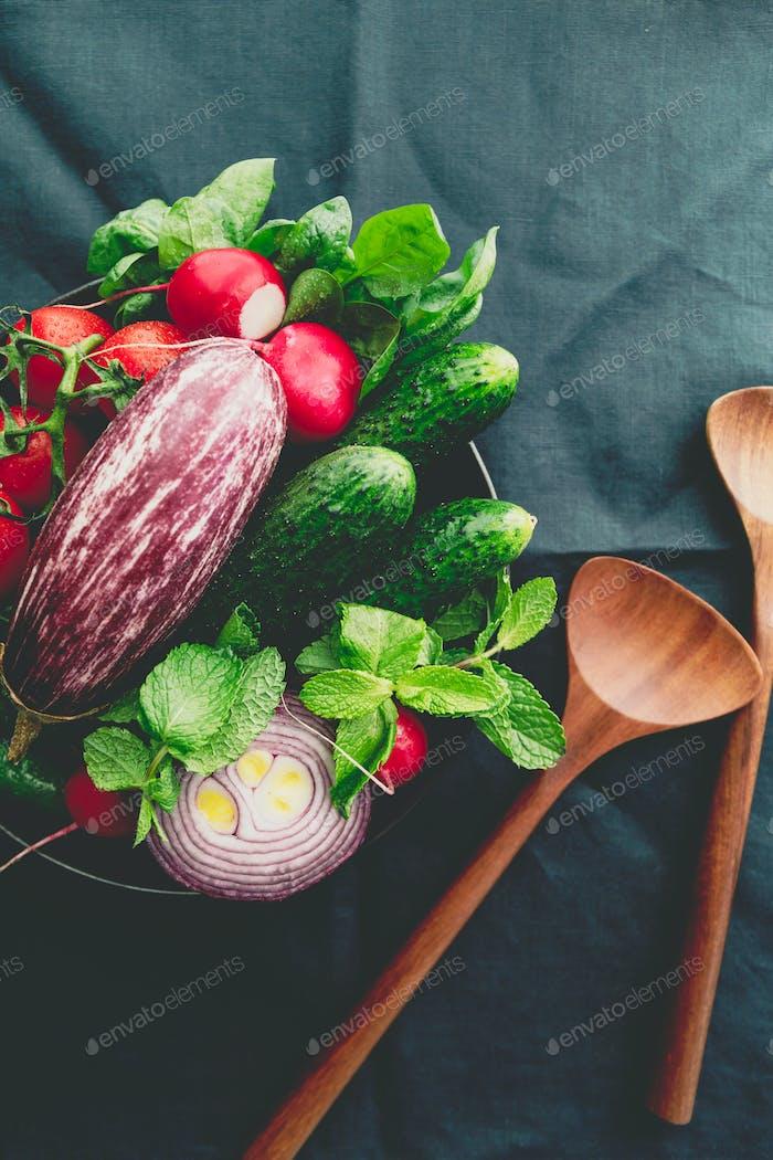 Verschiedene frisches buntes Gemüse in einem Teller auf einem Tisch mit hölzernen Küchenutensilien. Ansicht von oben.