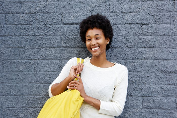 Smiling young woman standing against grey wall
