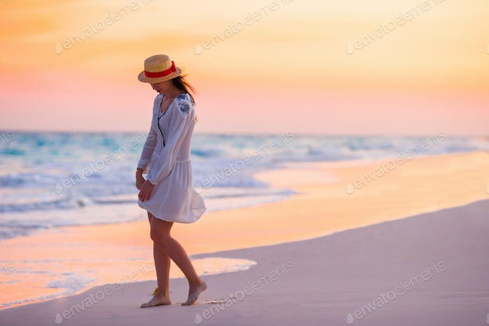 Young beautiful woman in sunset background of ocean