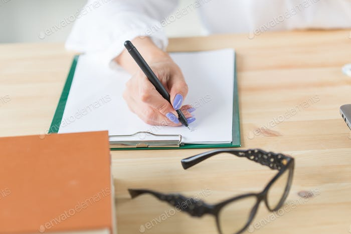 Working, business, office concept - close up of hand writing some notes and glasses lying near it