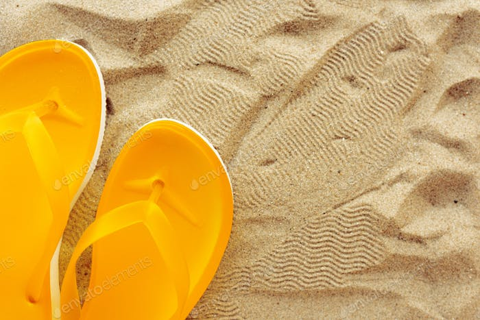 Yellow beach flip flops on sand
