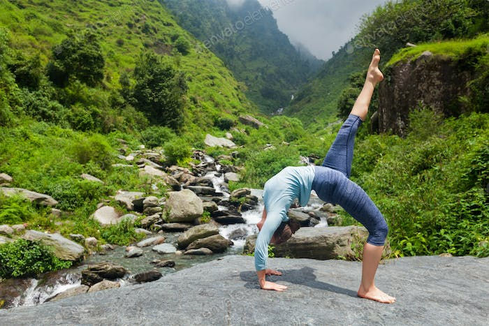 Woman doing yoga asana at waterfall