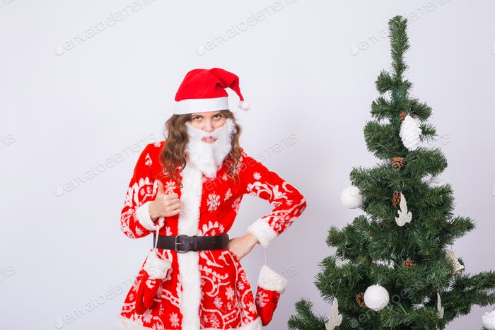 Christmas, fun and emotions concept - funny woman in santa suit and in artificial beard