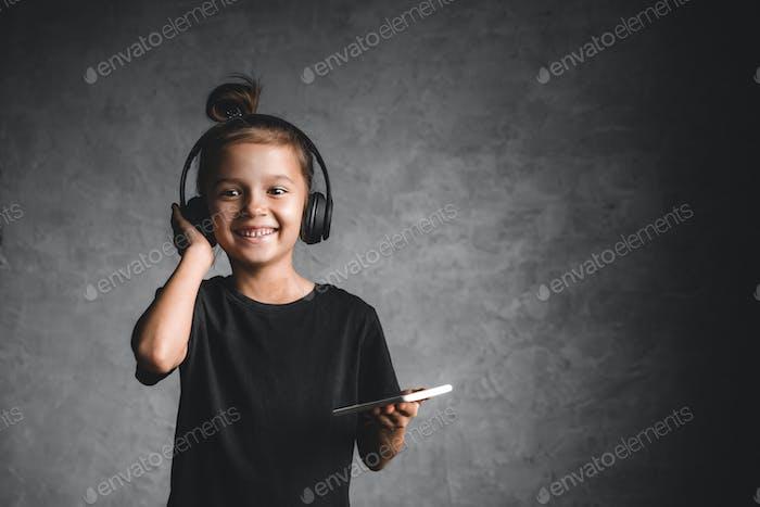 Kleines Mädchen mit Kopfhörern und Telefon auf einem grauen Hintergrund