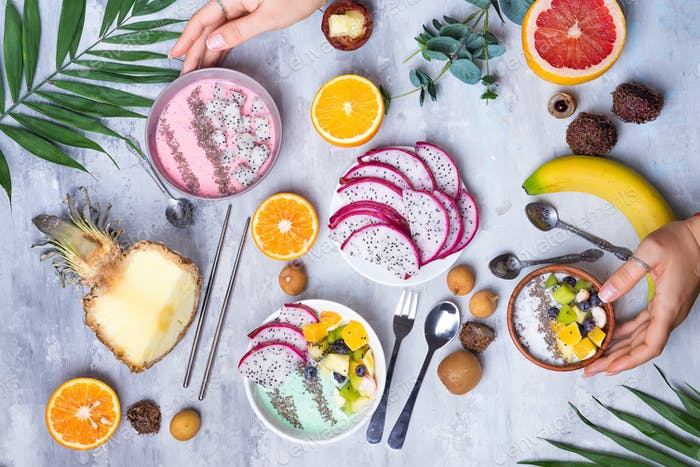 Breakfast table with yogurt acai bowls and fresh tropic fruits on a gray stone background with