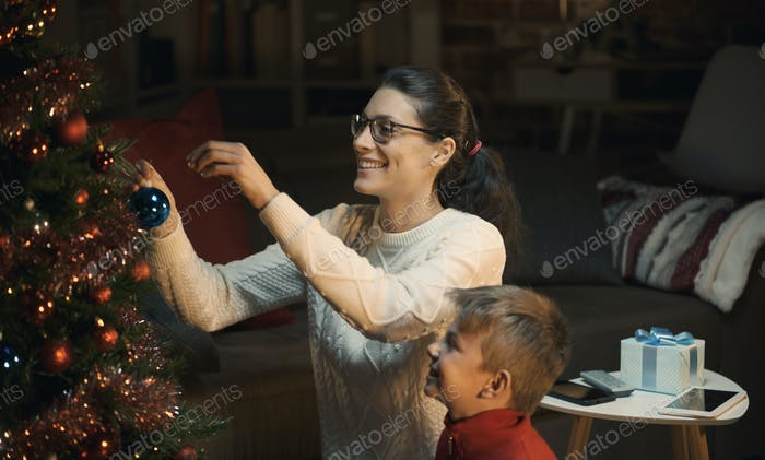 Mother and son decorating their Christmas tree together