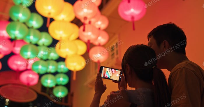Couple use of mobile phone to take photo of the chinese lantern